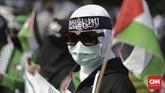 Salah seorang peserta aksi dengan ikat kepala hitam dan bertuliskan huruf Arab turut mengibarkan bendera Palestina.(CNN Indonesia/Adhi Wicaksono).