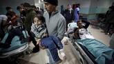 Seorang penduduk Palestina menggendong putrinya yang terluka di rumah sakit di Gaza bagian utara. Pasukan keamanan Israel di Gaza menyatakan aksi itu merupakan respons atas serangan roket dari Gaza ke Israel. (REUTERS/Mohammed Salem)