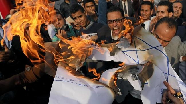Demonstran meneriakkan slogan anti-Amerika, anti-Israel dan anti-Trump serta membakar bendera Israel dalam aksi protes di Lawyers Syndicate,Kairo, Mesir pada 10 Desember2017. (REUTERS/Mohamed Abd El Ghany)