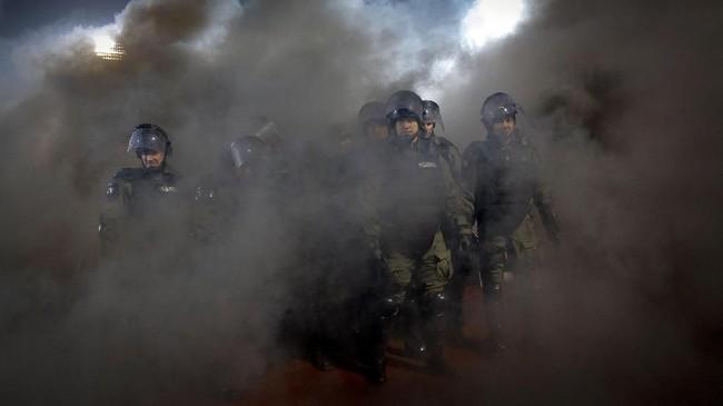 Petugas keamanan terlihat mengamankan kondisi di Stadion Partizana di tengah kepulan asap suar yang dinyalakan suporter. (AFP PHOTO / PEDJA MILOSAVLJEVIC)