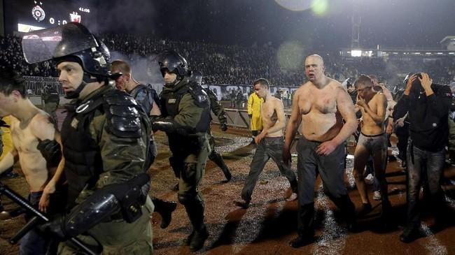 Petugas keamanan harus turun tangan untuk mengamankan kondisi di Stadion Partizana. Dikutip dari Fox Sports, menariknya kerusuhan justru terjadi antar kelompok suporter Partizan. (AFP PHOTO / PEDJA MILOSAVLJEVIC)