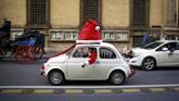 Seorang pria yang berpakaian seperti Santa Klaus membuyikan loncengnya sembari mengemudikan mobil Fiat 500 di kota Roma, Italla. (REUTERS/Alessandro Bianchi)