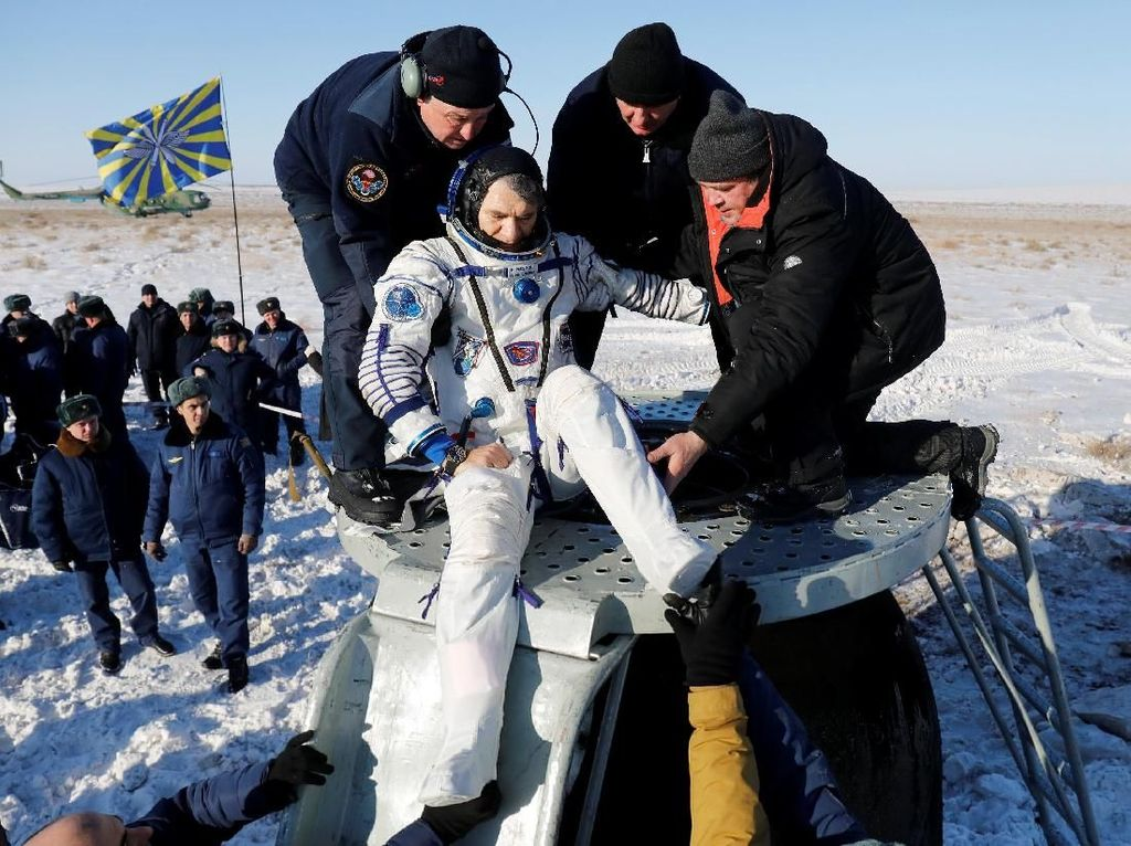 Astronot yang dibantu oleh tim untuk keluar dari kapsul saat mendarat di bumi.