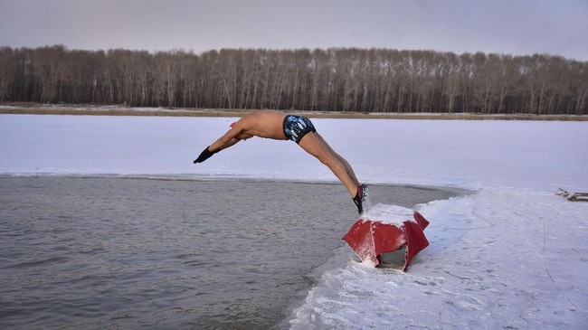 Seorang perenang musim dingin melompat ke sungai Songhua yang dikelilingi es di kota Songyuan, di Provinsi Jilin, China. (REUTERS/Stringer)