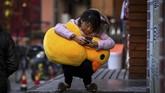 Seorang perempuan di Shanghai, China, berjongkok dengan mainan bebek di pangkuannya, sembari menggunakan telepon genggam. (AFP/CHANDAN KHANNA)