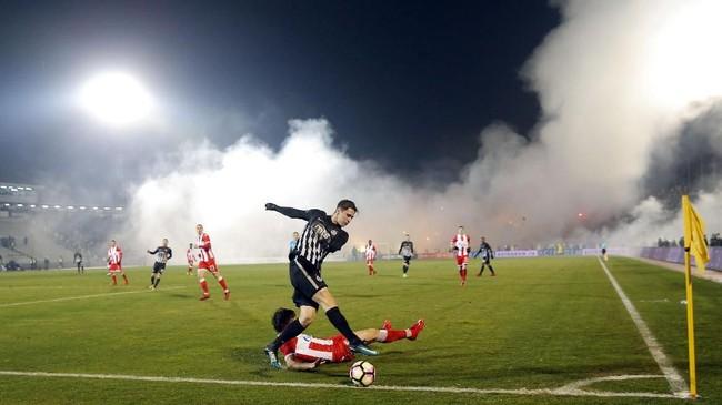 Derby Beograd antara Partizan vs Red Star dikenal sebagai Derby Abadi dan paling panas di kompetisi Liga Super Serbia. Terlihat, suar sudah dinyalakan sejak pertandingan di Stadion Partizana berlangsung. (AFP PHOTO / PEDJA MILOSAVLJEVIC)