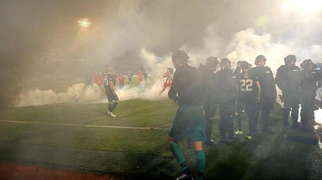 Suar kemudian mulai dilemparkan kedua kelompok suporter ke dalam Stadion Partizana usai kedudukan imbang 1-1. Pertandingan pun dihentikan sejenak. (AFP PHOTO / PEDJA MILOSAVLJEVIC)