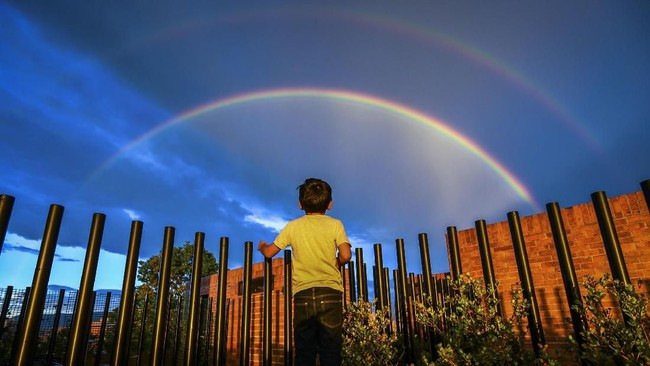 Seorang bocah melihat pelangi ketika matahari terbenam di kota Bogota, Kolombia. Pelangi pernah hadir dalam puisi Pablo Neruda.