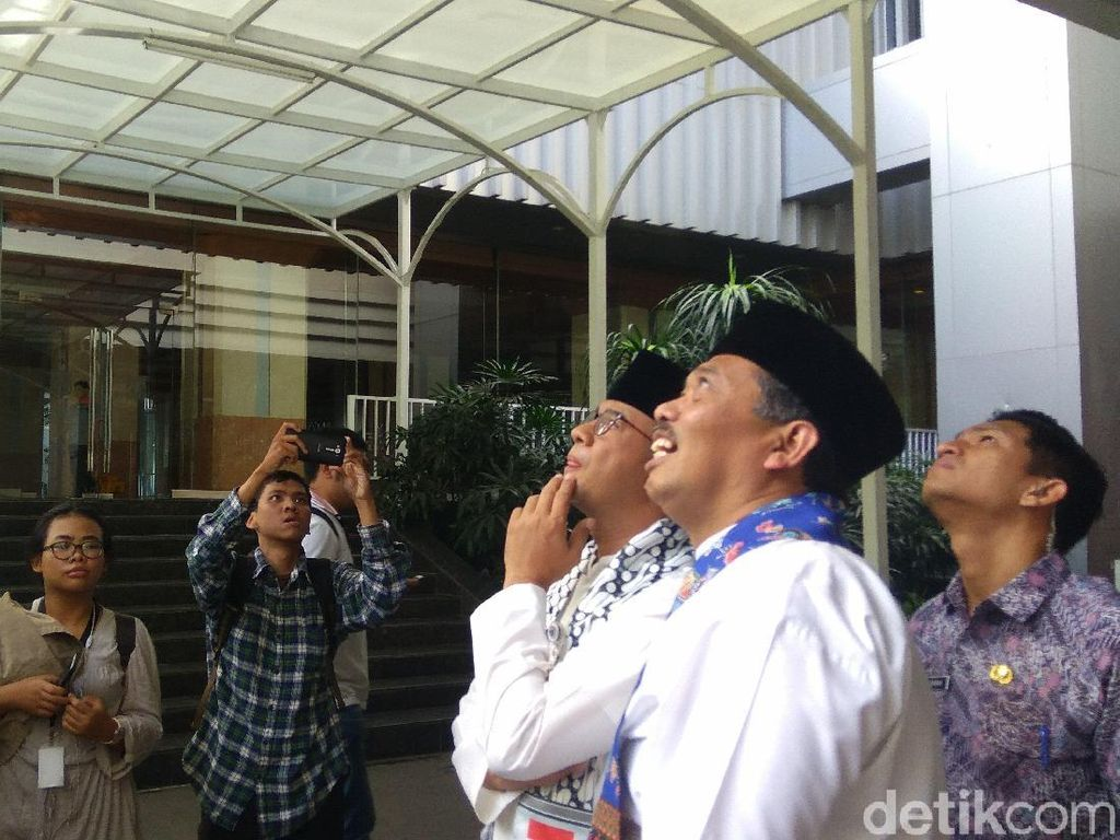 Anies yang didampingi Kabiro Umum Setda DKI Jakarta Firmansyah berjalan ke arah Gedung Blok G. Dari bawah Anies nampak melihat ke arah Gedung DPRD DKI Jakarta.   Foto: Zhacky/detikcom