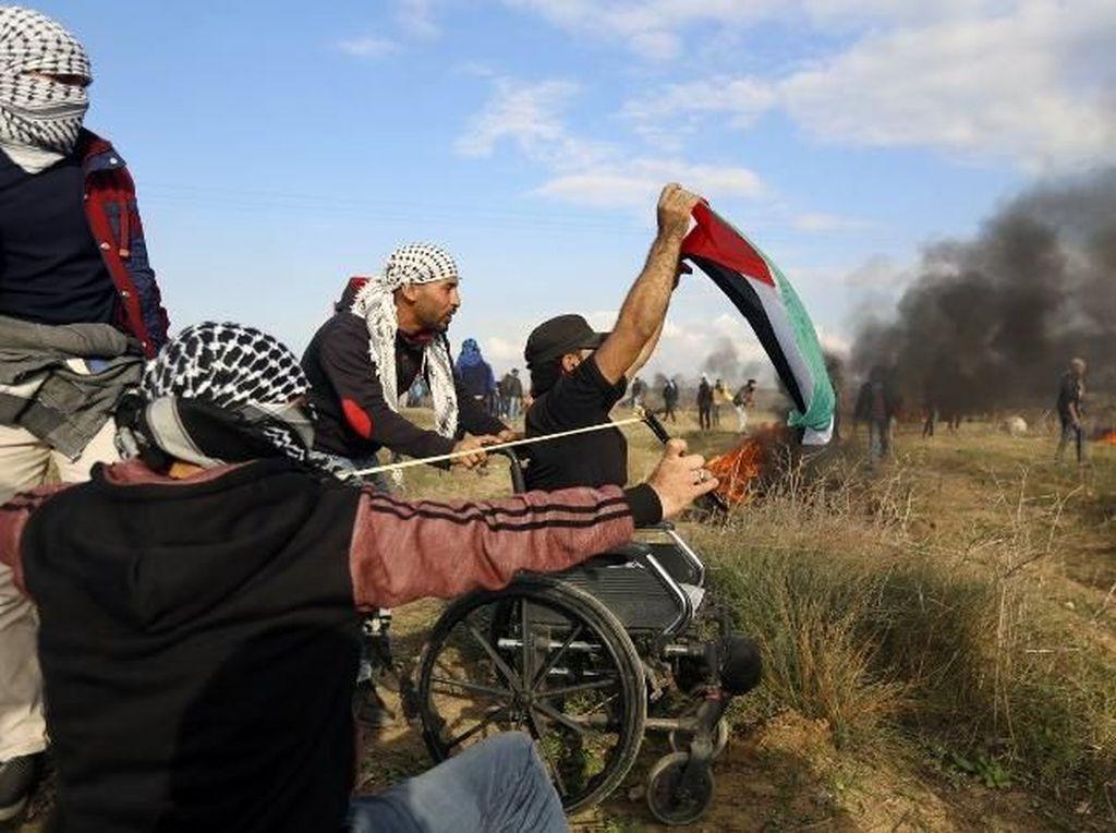 Thurayeh membawa bendera Palestina dan melambaikannya ke arah tentara Israel di perbatasan. Sejumlah saksi mata dan jurnalis yang melihatnya menyebut Thurayeh sempat memanjat tiang listrik untuk mengibarkan bendera Palestina. Foto: AFP PHOTO/MOHAMMED ABED