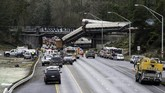 Sebanyak 13 dari 14 gerbong penumpang kereta itu terjungkal dari sebuah jembatan ke jalan yang berada di bawah jembatan. Sedikitnya lima mobil dan dua truk terkena dampak kecelakaan. (AFP Photo/KathrynElsseser)