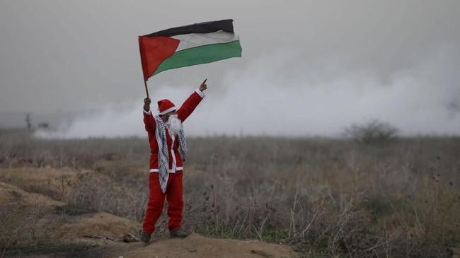 Seorang demonstran berpakaian seperti Sinterklas sambil memegang bendera Palestina ketika tentara Israel menyemprotkan gas air mata dalam demonstrasi memprotes keputusan Presiden AS Donald Trump yang mengakui Yerusalem sebagai ibu kota Israel di timur Gaza, sekat perbatasan dengan Israel, Selasa (19/12). (Reuters /Mohammed Salem)