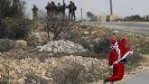 Selain di Gaza, para demonstran berkostum Sinterklas juga beraksi di Ramallah, Tepi Barat. Mereka melemparkan batu ke arah militer Israel. (Reuters/Mohamad Torokman)