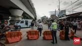 Petugas Dishub, mengarahkan kendaraan pribadi menghindar dari jalur depan Stasiun Tanah Abangyang diperuntukkan sebagai lahan ratusan PKL. (CNN Indonesia/Adhi Wicaksono).