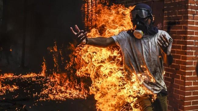 Seorang demonstran anti-pemerintah Presiden Nicolas Maduro tersambar api setelah sebuah tangki gas motor polisi meledak dalam bentrokan di Caracas, Venezuela 3 Mei 2017. (AFP PHOTO/JUAN BARRETO)