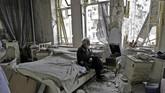 Mohammed Mohiedin Anis alias Abu Omar, 70 tahun, merokok dengan tenang sambil duduk mendengarkan musik di kamar tidurnya yang hancur berantakan di bekas kawasan yang dikuasai pemberontak, Al-Shaar, Aleppo, Suriah. (AFP PHOTO / JOSEPH EID)