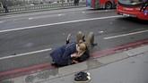 Seorang wanita membantu korban luka-luka dalam serangan teror di Jembatan Westminster London, Inggris, 22 Maret 2017. Empat orang tewas termasuk pelaku, sedikitnya 40 luka-luka. (REUTERS/Toby Melville)