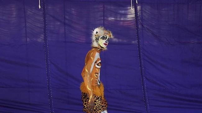 Seorang seniman dilukis wajahnya sehingga terlihat seperti harimau yang sedang berjalan menuju sebuah panggung dalam acara kesenian di Bengaluru, India. (Reuters/Abhishek N. Chinnappa)