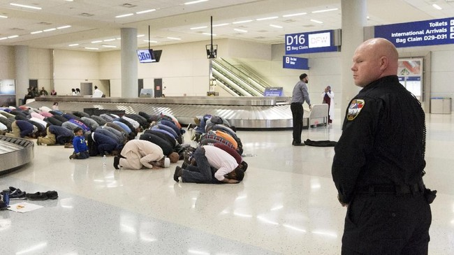 <p>Umat muslim sembahyang di lokasi pengambilan bagasi sebagai protes atas larangan bepergian yang berlaku akibat perintah eksekutif dari Presiden Amerika Serikat Donald Trump di Bandara International Fort Worth, Dallas, Texas, 29 Januari 2017. (REUTERS/Laura Buckman)</p>