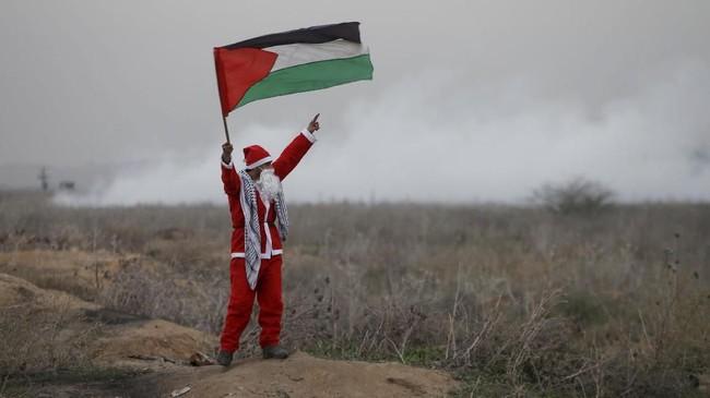 Seorang demonstran berpakaian Santa Claus mengibarkan bendera Palestina dalam aksi protes melawan keputusan Presiden Amerika Serikat Donald Trump untuk mengakui Yerusalem sebagai Ibu Kota Israel, foto diambil di Jalur Gaza, 19 Desember 2017. (REUTERS/Mohammed Salem)