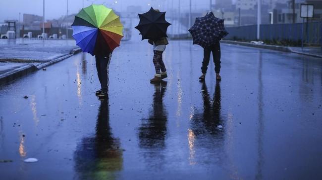 Anak-anak Palestina berjalan menggunakan payung dalam hari Natal yang hujan di kota Gaza. (AFP/Mohammed Abed)
