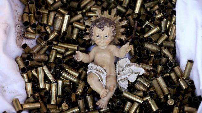 Patung bayi Yesus terbaring di kasur yang terbuat dari selongsong-selongsong peluru di Basiliki Santa Francis di Assisi, Italia. Total 445 selongsong peluru menjadi simbol jumlah pendeta, biarawati dan biarawan yang terbunuh sejak tahun 2000 untuk membela keyakinan mereka. (Reuters/Alessandro Bianchi)