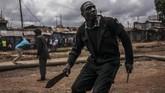Bentrokan antara demonstran dengan aparat keamanan saat pemilihan umum ulang di Kibera, Nairobi, Kenya pada 26 Oktober 2017. Sedikitnya 11 orang tewas dalam kericuhan pemilu yang paling memecah belah di Kenya tersebut. (AFP PHOTO/MARCO LONGARI)