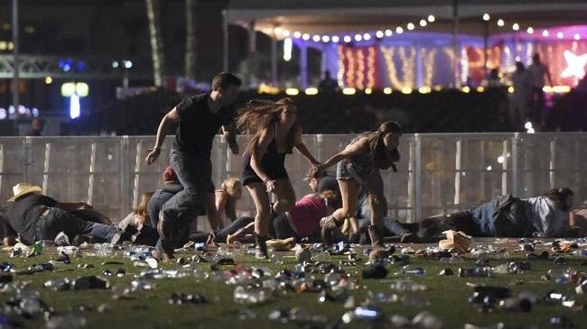 Orang-orang berlarian menyelamatkan diri saat pelaku menembaki para penonton festival musik dari atas Hotel dan Kasino Mandalay Bay, sebuah resort di Las Vegas, Nevada, AS, Minggu, 1 Oktober 2017. Sedikitnya 58 tewas dan 515 luka-luka. David Becker/Getty Images/AFP