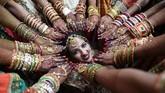 Seorang pengantin perempuan di India berpose di sebuah pernikahan massal sementara yang lain menunjukkan tangan yang sudah dihiasi. Pernikahan ini digelar di Surat, 270 kilometer dari Ahmedabad. Total 251 pasangan menikah pada acara yang digelar badan amal grup PP Savani dan Movaliya. (AFP/Sam Panthaky)