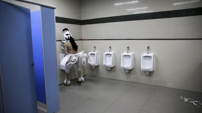 Seorang penari menggunakan kamar kecil di sela-sela penampilannya di sebuah stadion di Bangkok, Thailand. (Reuters/Athit Perawongmetha)