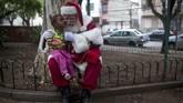 Seorang yang berkostum Sinterklas berpose dengan seorang gadis kecil dalam sebuah acara yang merayakan akhir dari musim Natal di kota Rio de Janeiro, Brasil. Perayaan ini selalu digelar setiap tahun, satu hari setelah Natal, oleh sekolah yang mendidik para Sinterklas 'profesional'. (AFP/Mauro Pimentel)