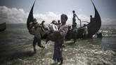 Seorang pria Bangladesh membantu pengungsi muslim Rohingya turun dari perahu menuju Teknaf, 30 September 2017. Operasi militer di Rakhine menyebabkan sedikitnya 650 ribu warga Rohingya mengungsi ke Bangladesh dan menciptakan krisis kemanusiaan yang hingga kini belum usai. (AFP PHOTO/FRED DUFOUR)