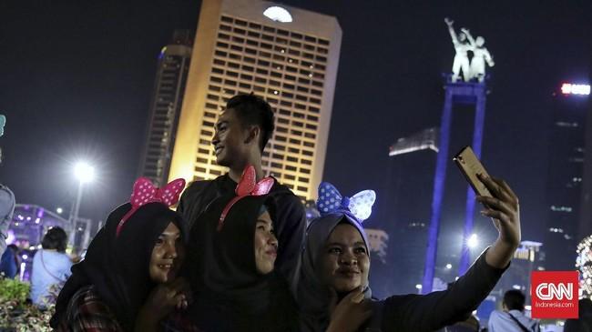 Sebagian warga pun memilih untuk tetap berada di lokasi keramaian bersama teman atau keluarganya hingga sekitar satusampai dua jam setelah tahun berganti.(CNN Indonesia/ Hesti Rika)