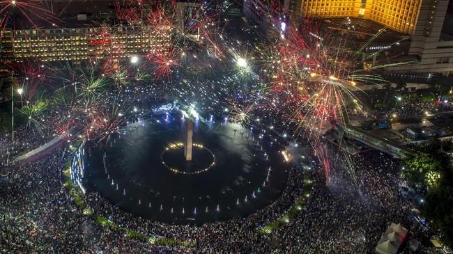 <p>Saat detik-detik menjelang pergantian tahun, ratusan kembang api yang dinyalakan warga pun bersahutan memecah keheningan di langit di sekitar Bundaran HI dan Patung Selamat Datang. (AFP PHOTO/BAY ISMOYO)</p>
