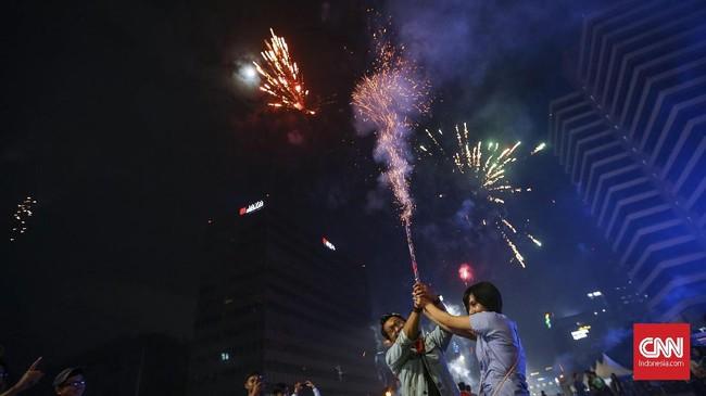 <p>Selain panggung hiburan, Jakarta diramaikan dengan warga yang membawa dan menyalakan kembang api, baik yang berukuran kecil maupun besar. (CNNIndonesia/Safir Makki)</p>