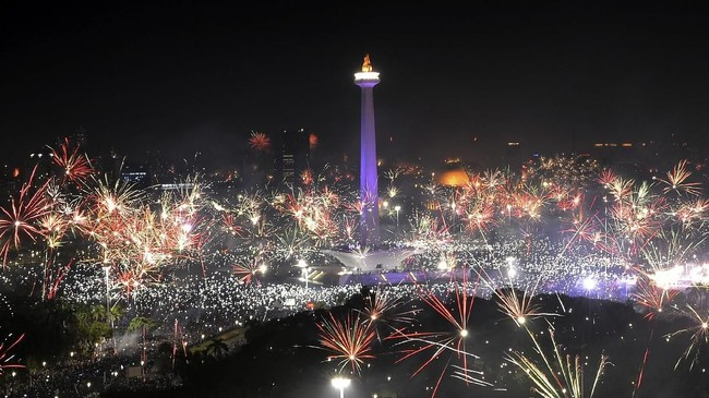 <p>Ingar bingar kembang api juga terdengar bersahutan di kawasan Monumen Nasional. Percikan api menciptakan semburat warna di angkasa bercampur dengan kerlip lampu di sekitar lokasi keramaian itu. (ANTARA FOTO/Wahyu Putro A)</p>
