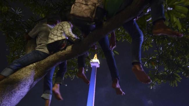 Beberapa warga bahkan memilih cara tak lazim untuk melihat perayaan Tahun Baru di pusat keramaian. Sebagian dari mereka menaiki pohon untuk menyaksikan panggung hiburan lebih jelas dari kejauhan. (ANTARA FOTO/Wahyu Putro A)