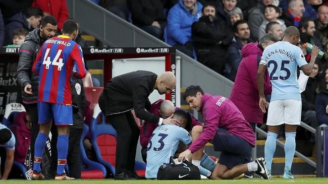 <p>Manajer Manchester City Pep Guardiola berusaha menghibur Gabriel Jesus yang menangis setelah mengalami cedera lutut. Jesus dikabarkan akan absen satu bulan. (REUTERS/David Klein)</p>