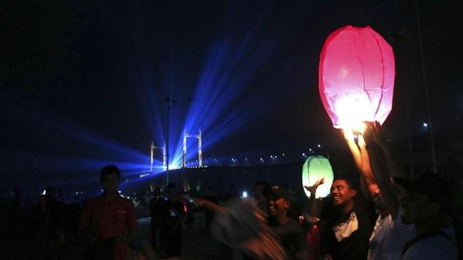 <p>Berbeda dengan di Aceh, sejumlah warga melepas lampion berwarna-warni saat pergantian Tahun Baru 2018 di kawasan Jembatan Merah Putih, Ambon, Maluku. (ANTARA FOTO/izaac mulyawan/aww/18)</p>