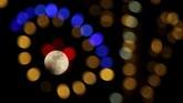 Supermoon yang diambil diantara kerlap=kerlip lampu hiasan Natal di Valletta, Malta. (REUTERS/Darrin Zammit Lupi)