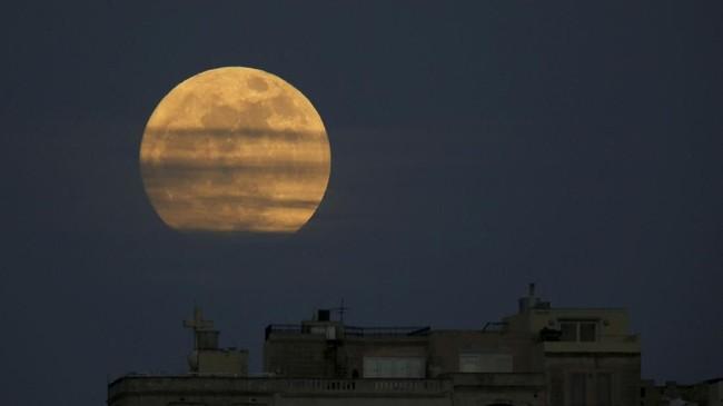 <p>Supermoon saat baru terbit di Pieta, Malta.Supermoon terjadi saat orbit bulan purnama ada di titik terdekat dengan bumi. (REUTERS/Darrin Zammit Lupi)</p>
