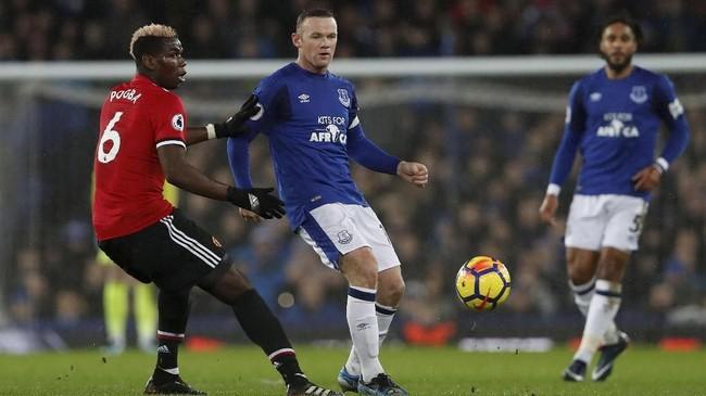 Penyerang Everton Wayne Rooney dijaga ketat gelandang Manchester United Paul Pogba. Hingga akhir babak pertama tidak ada gol yang tercipta di Stadion Goodison Park. (Reuters/Lee Smith)