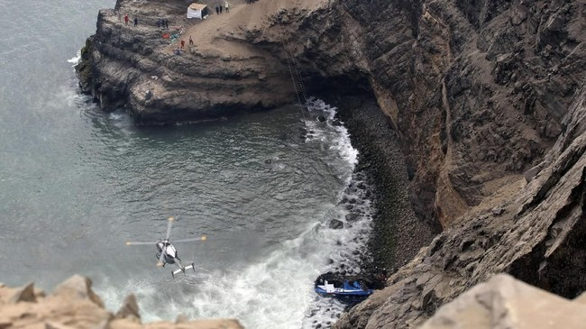 Helikopter membantu tim penyelamat untuk mengangkut para korban setelah sebuah bus bertabrakan dengan sebuah truk dan meluncur dari tebing di sepanjang jalan raya yang membelok tajam di utara Ibu Kota, Lima. (REUTERS/Guadalupe Pardo)