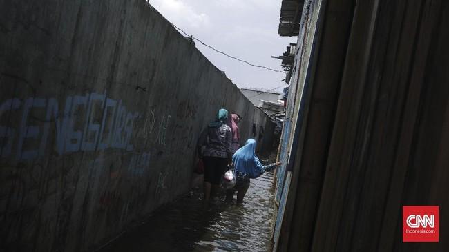 <p>Warga menembus banjir rob di kawasan Pelabuhan Muara Angke. Wilayah permukiman nelayan tersebut digenangi air laut hingga setinggi 15 sentimeter. (CNN Indonesia/ Hesti Rika)</p>