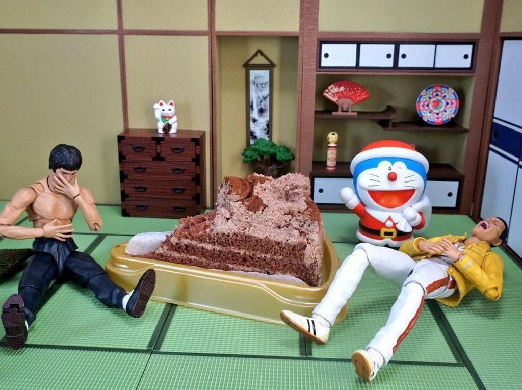 Freddie tampak tak kuat menghabiskan kue tersebut sementara Bruce hampir muntah hingga muncul Doraemon. Dok. Twitter/@suekichiii