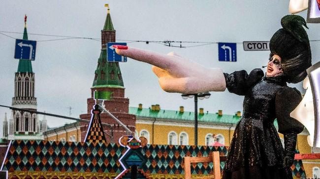 Seorang seniman jalanan di jalan Tverskaya, tepatnya di depan Istana Kremlin, Moskow, mengangkat tangan raksasanya dalam festival menyambut natal dan tahun baru. Rusia sendiri merayakan natal kristen ortodoks pada 7 Januari. (AFP PHOTO / Mladen ANTONOV)