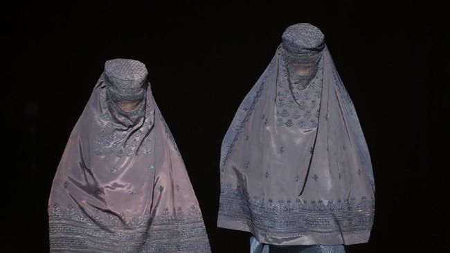 Dua perempuan Afghanistan mengenakan burka berjalan meninggalkan toko di sebuah pasar di Mazar-i-Sharif. (AFP PHOTO / FARSHAD USYAN)