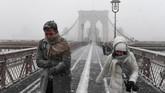Badai salju juga menyebabkan ribuan penerbangan ditangguhkan atau dibatalkan. Para pejalan kaki harus berjuang melintasi angin bersalju di Jembatan Brooklyn saat Badai Salju Grayson melanda Kota New York, Amerika Serikat, 4 Januari 2018. (REUTERS/Darren Ornitz)