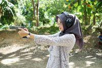 Di foto tersebut, Indah Nada Puspita tengah menjajal olahraga menembak.