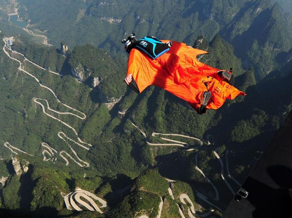 Wingsuit Flying. Aktivitas ini menggunakan pakaian terbang yang dibuat khusus untuk membuat pemakainya bisa mendapat daya angkat udara dan bermanuver lebih lama saat melayang. Diawali dengan lompatan dari daratan tinggi, tebing, atau pesawat, Wingsuit Flying diakhiri dengan si penerbang membuka payung parasut. (VCG/VCG via Getty Images)